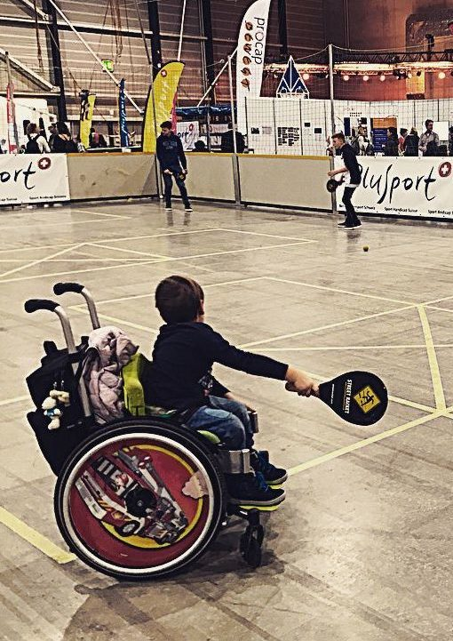 photo of child in wheelchair playing Street Racket