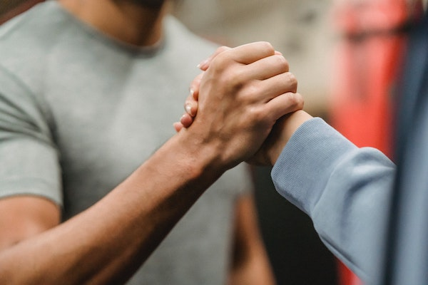 photo of man and woman facing each other and clenching hands in mutual support